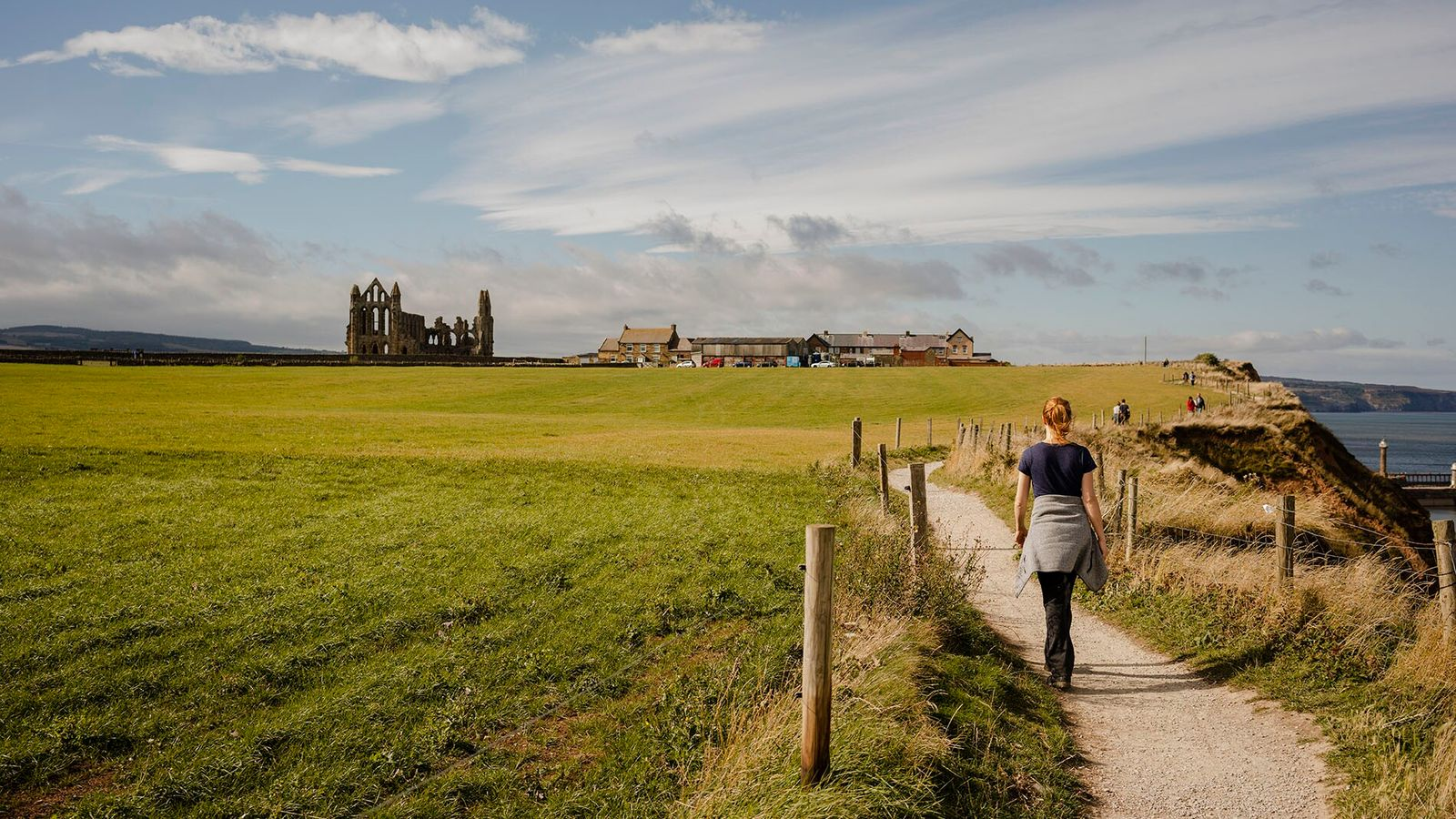 A woman walks along the scenic path between Whitby and Robinshood Bay.