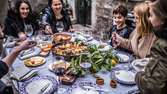 A family tucks in to peka, a uniquely Balkan way of cooking. Meat and potatoes are ...