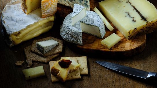When creating a cheese board, the cheeses should ideally be served simply, alongside plain crackers.