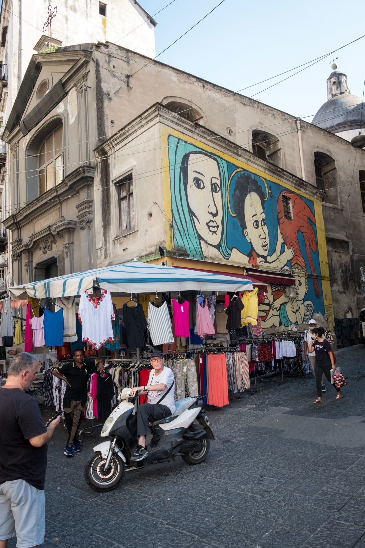 The daily market in Via Vergini, where clothes stalls are set up in front of street ...