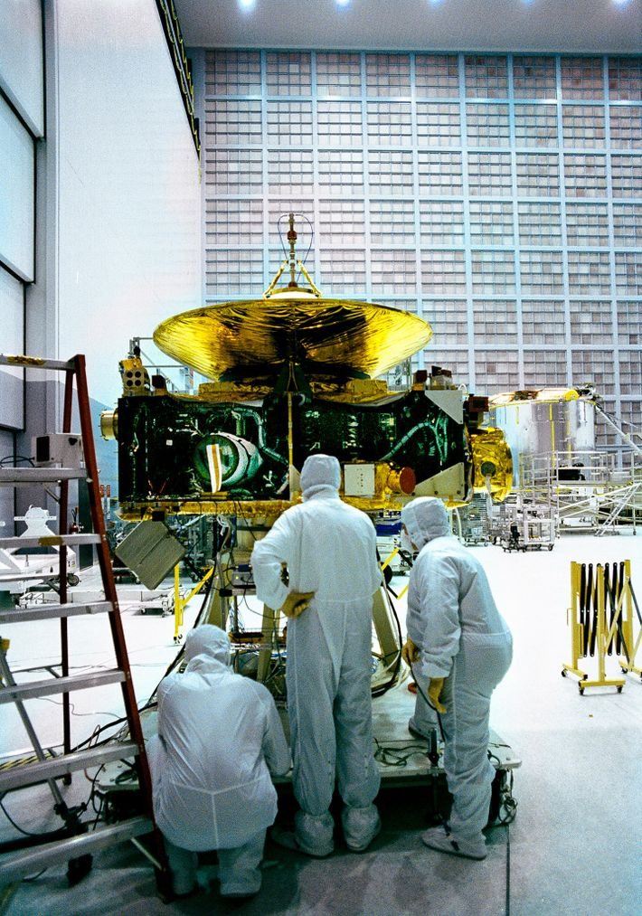 At NASA Goddard Space Flight Centre, technicians in clean-room gear carefully assemble the New Horizons spacecraft ...