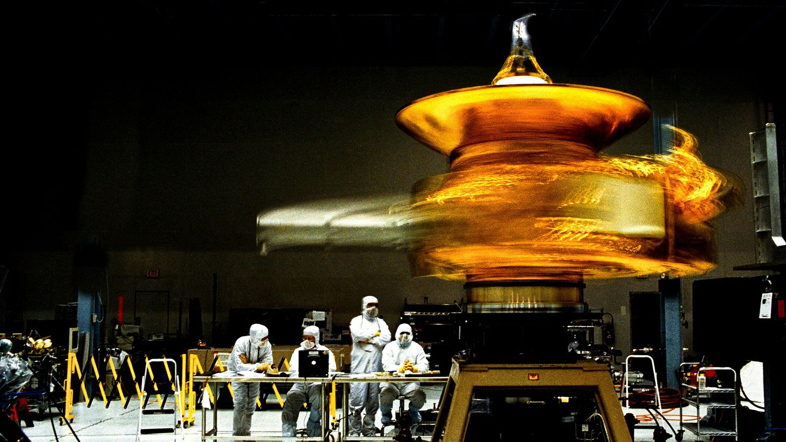 Technicians gaze as New Horizons pirouettes like a ballerina in this July 2005 test of the ...