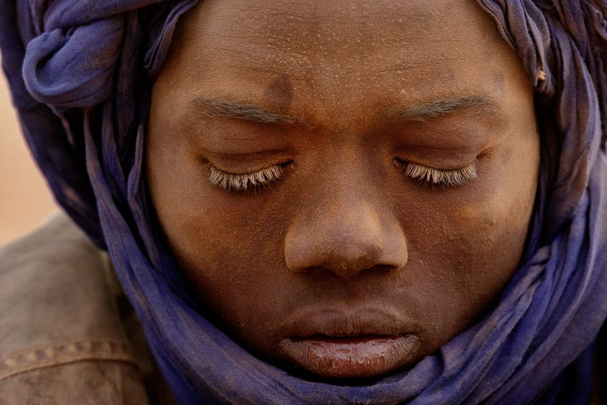 A teenager is dusted with sand from toiling in a mine. He is one of many ...