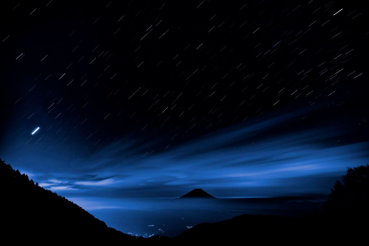 A seven-minute exposure creates star trails above a dwarfed Mount Fuji, as seen from the Ikeno-Chaya ...