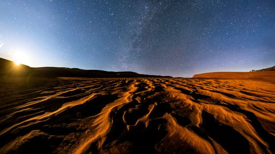 Moonlight shines on the surreal landscape of Colorado's Great Sand Dunes National Park. Though astronauts in ...