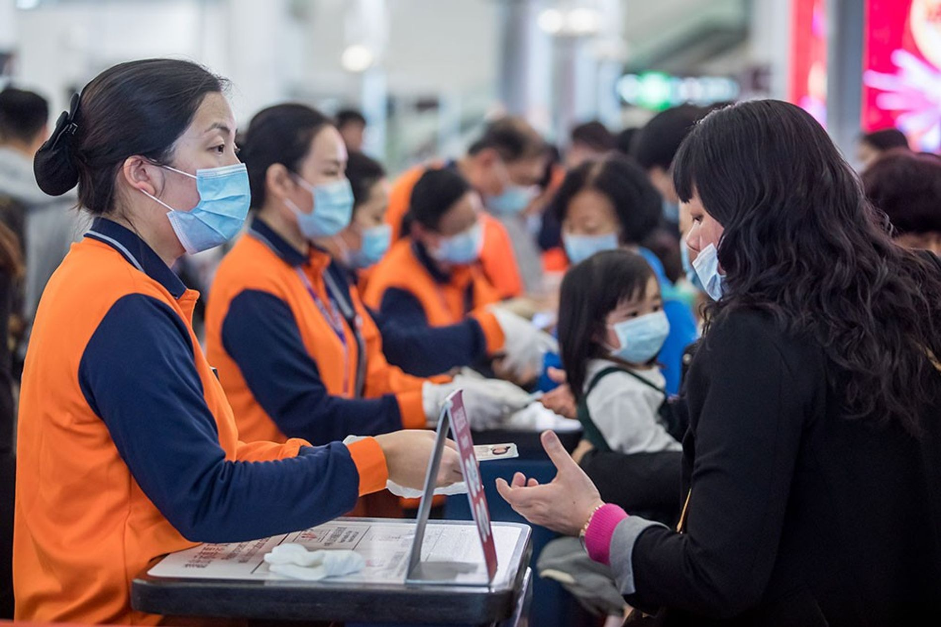 Hong Kong railway workers, in orange vests and face masks, check IDs of travelers at its ...