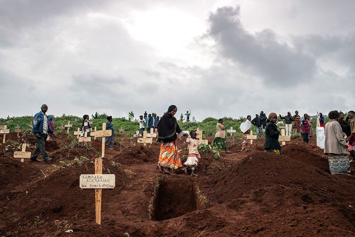 Clouds gathered thickly over the lines of mourners picking their way between recently covered graves as ...