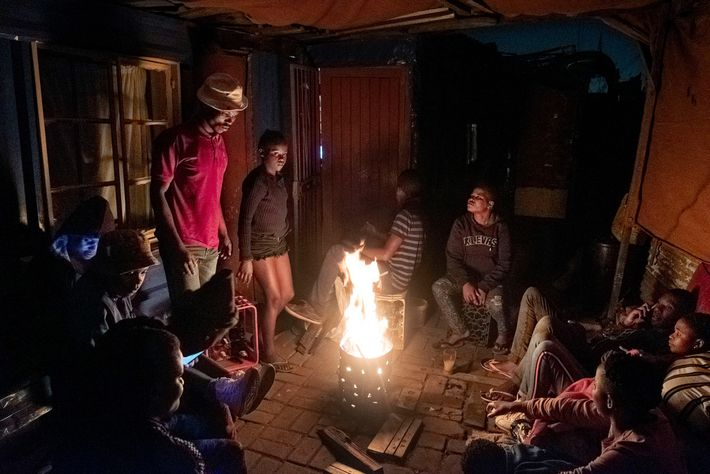 Friends and family sit outside on a Saturday night to keep warm in Thokoza, a township ...