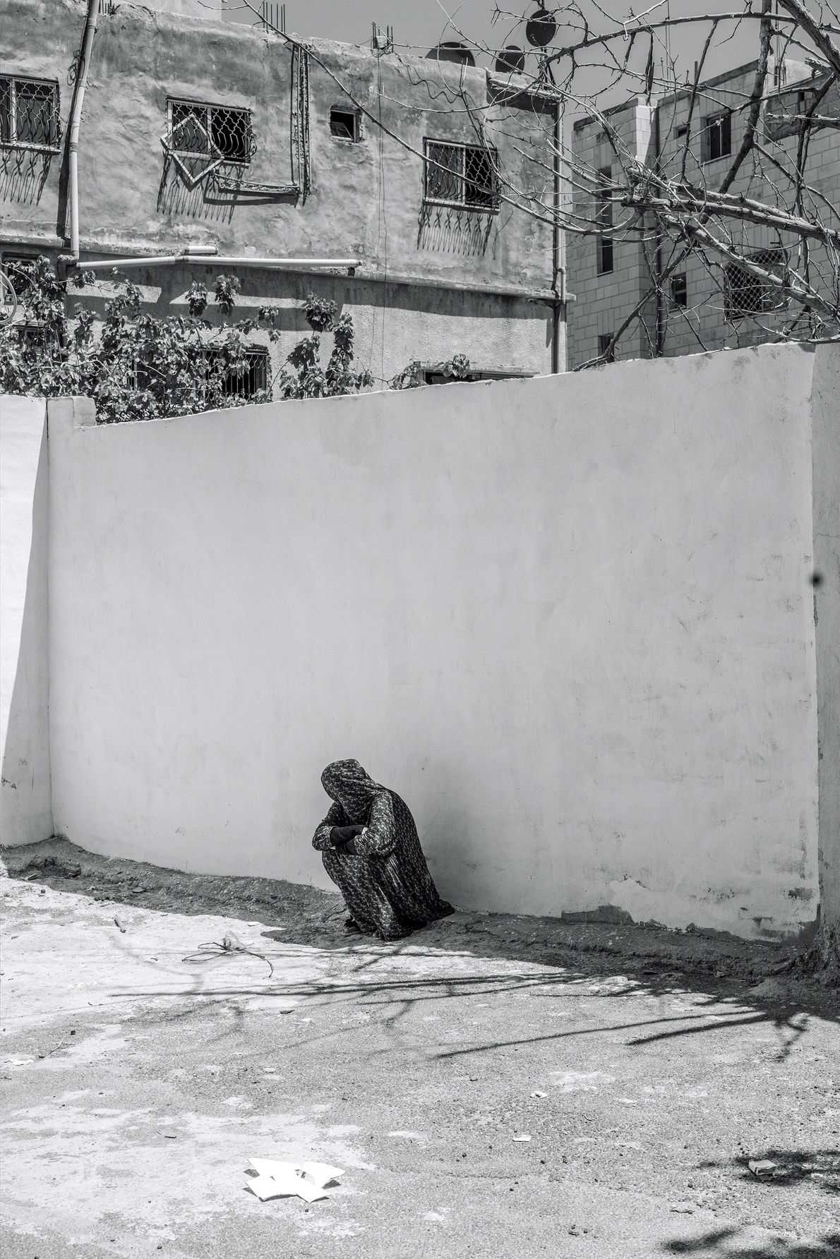 A woman sits under the shade of a wall in the courtyard of an Islamic charity ...