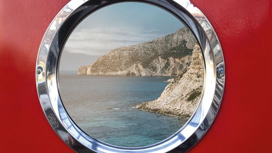 Porthole on a ship showcasing striking view of cliffs.