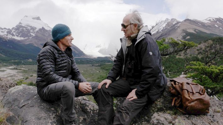 Nomad crewmember Alberto Castillo chats with Herzog. At Herzog's side is Bruce Chatwin's leather rucksack, which ...