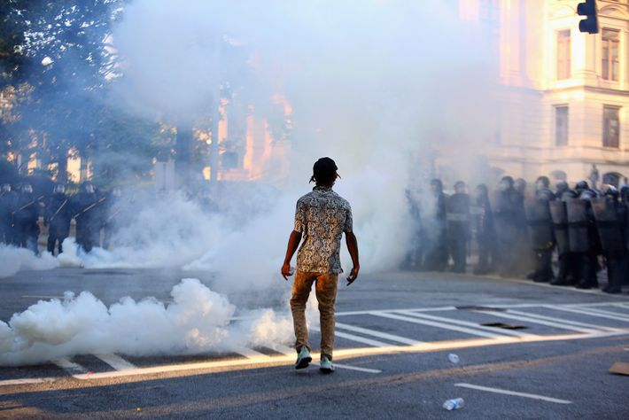 A protester stands amidst tear gas during a protest in Atlanta against the killing of George ...