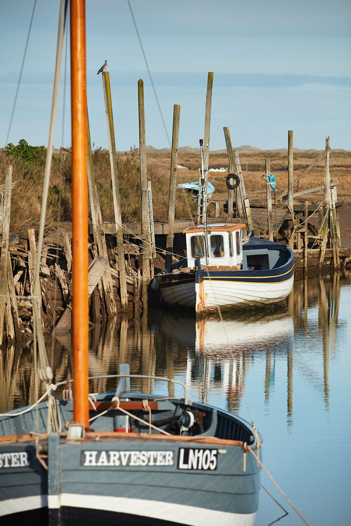 Boats moored in the shallows at Blakeney, a picturesque fishing village that was a busy seaport ...