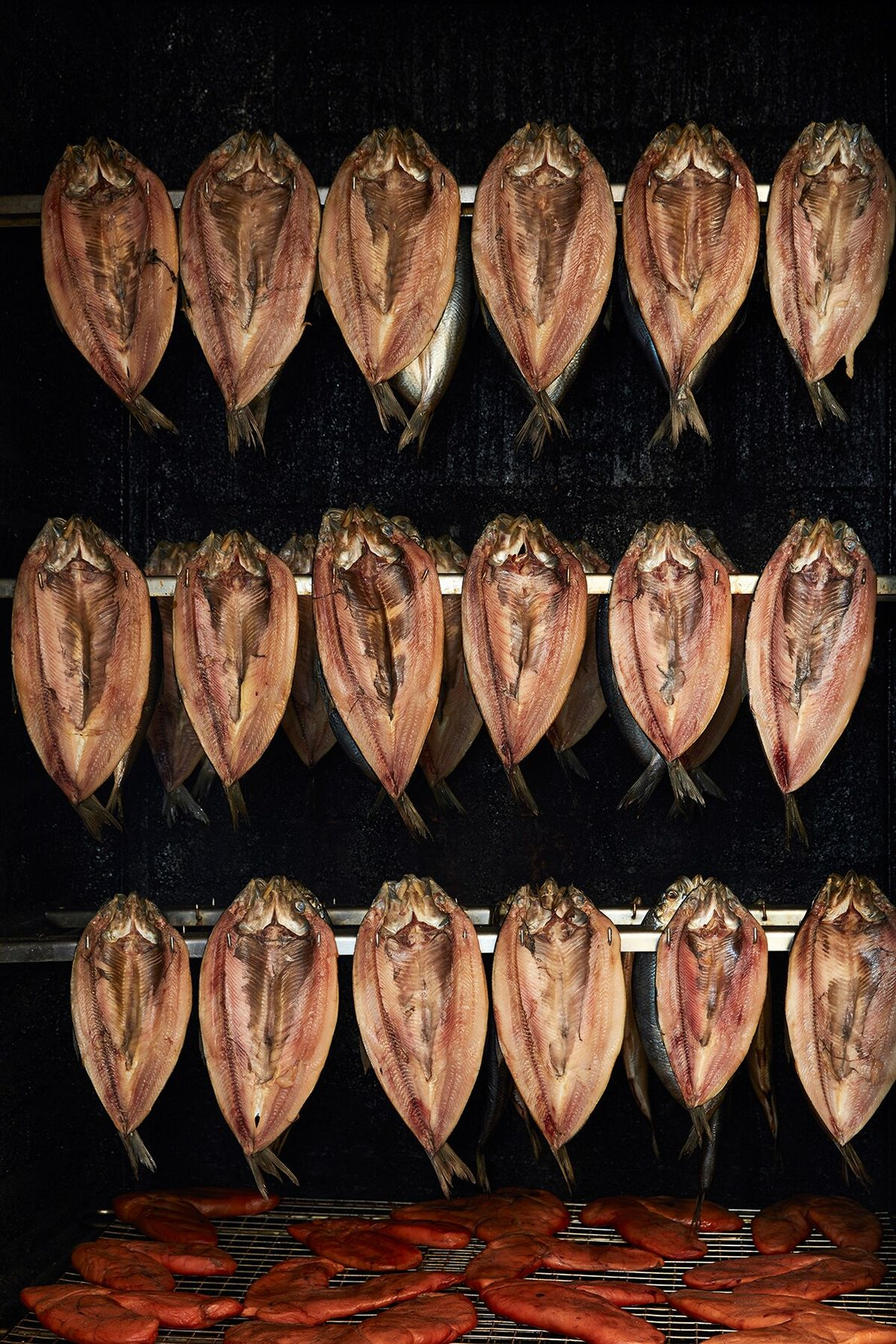 Kippers hanging in the smoker at the Cley Smokehouse. The pungent fish is a signature product ...