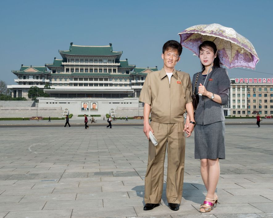 A couple poses in the middle of Kim Il Sung Square, which can fit an estimated ...