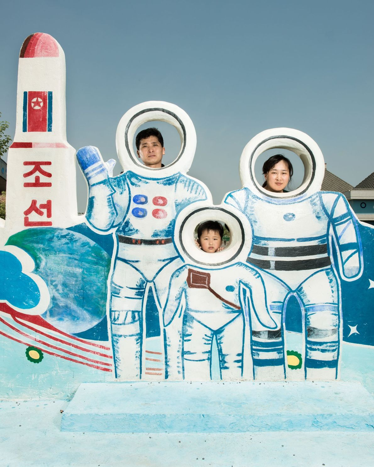 A family poses behind a tribute to the North Korean space program at a water park ...