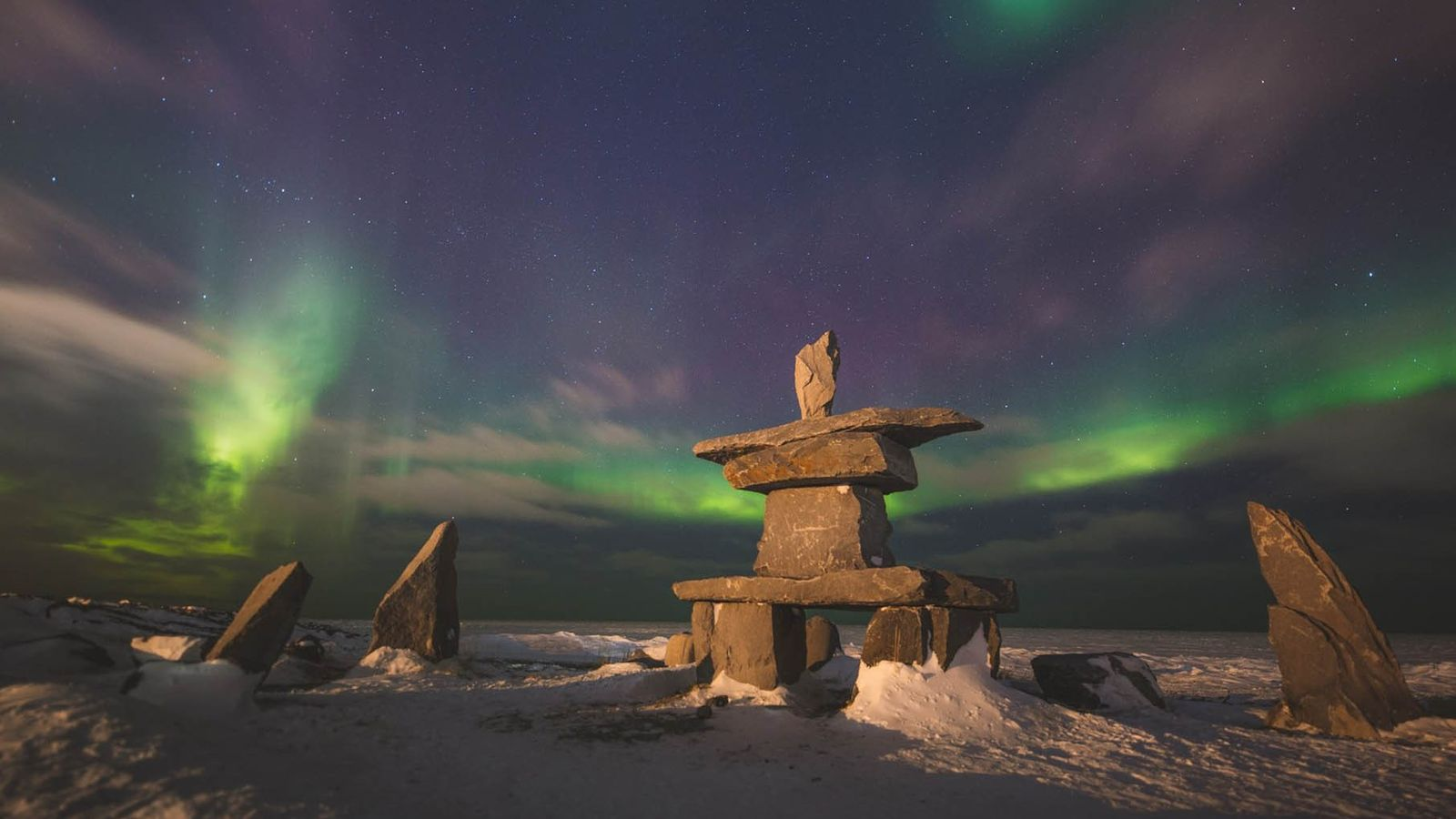 Northern Lights over Inukshuk, a structure of rough stones traditionally used by Inuit people as a ...