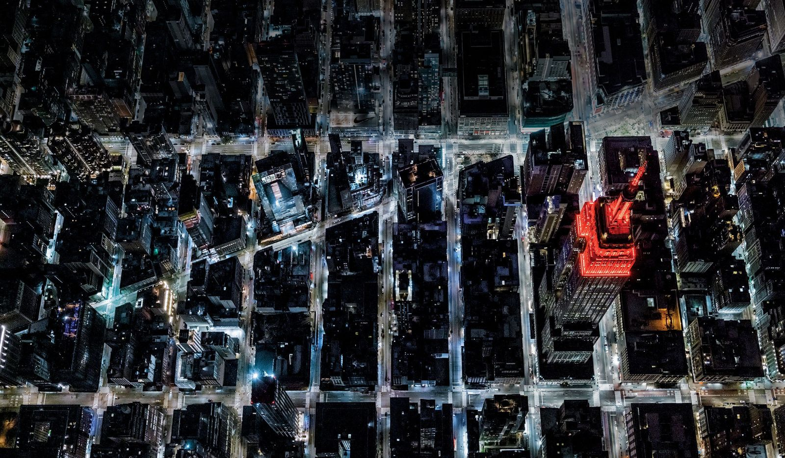New York City's streets stand deserted under lockdown, April 2020. The Empire State Building is lit ...