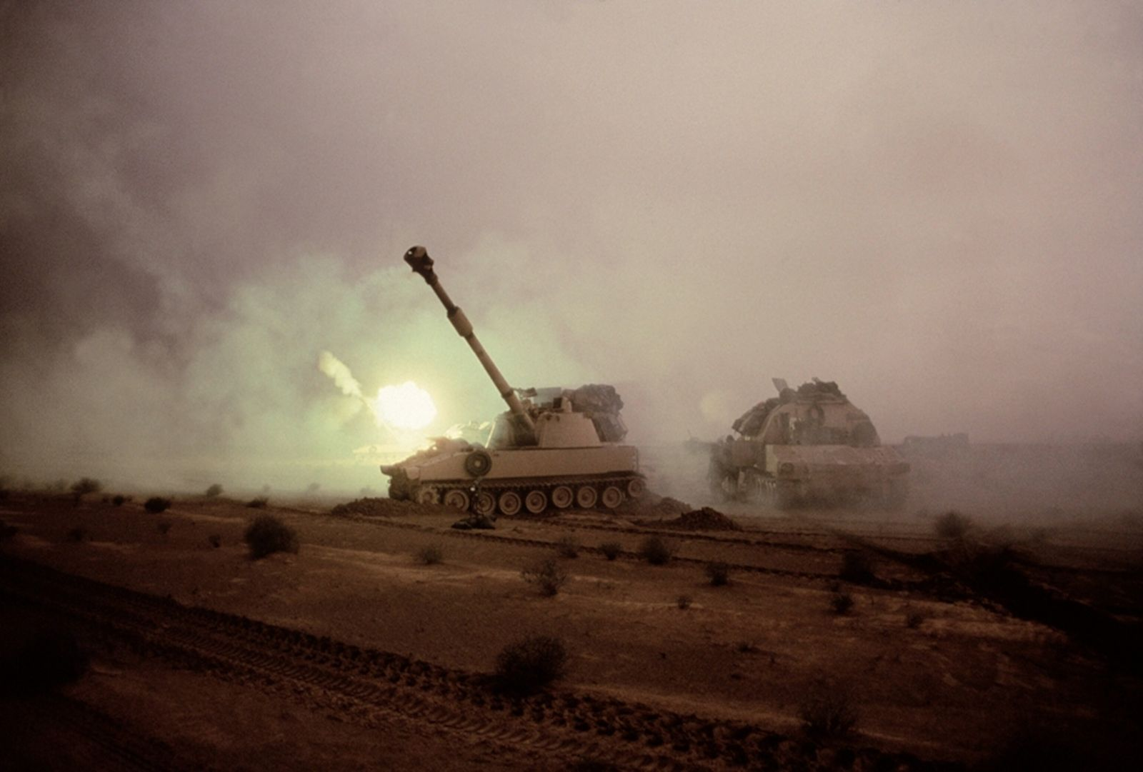 A M1A1 tank lofts a round toward Iraqi positions. The tank's enourmous cannon fired dart-shaped shells—some ...