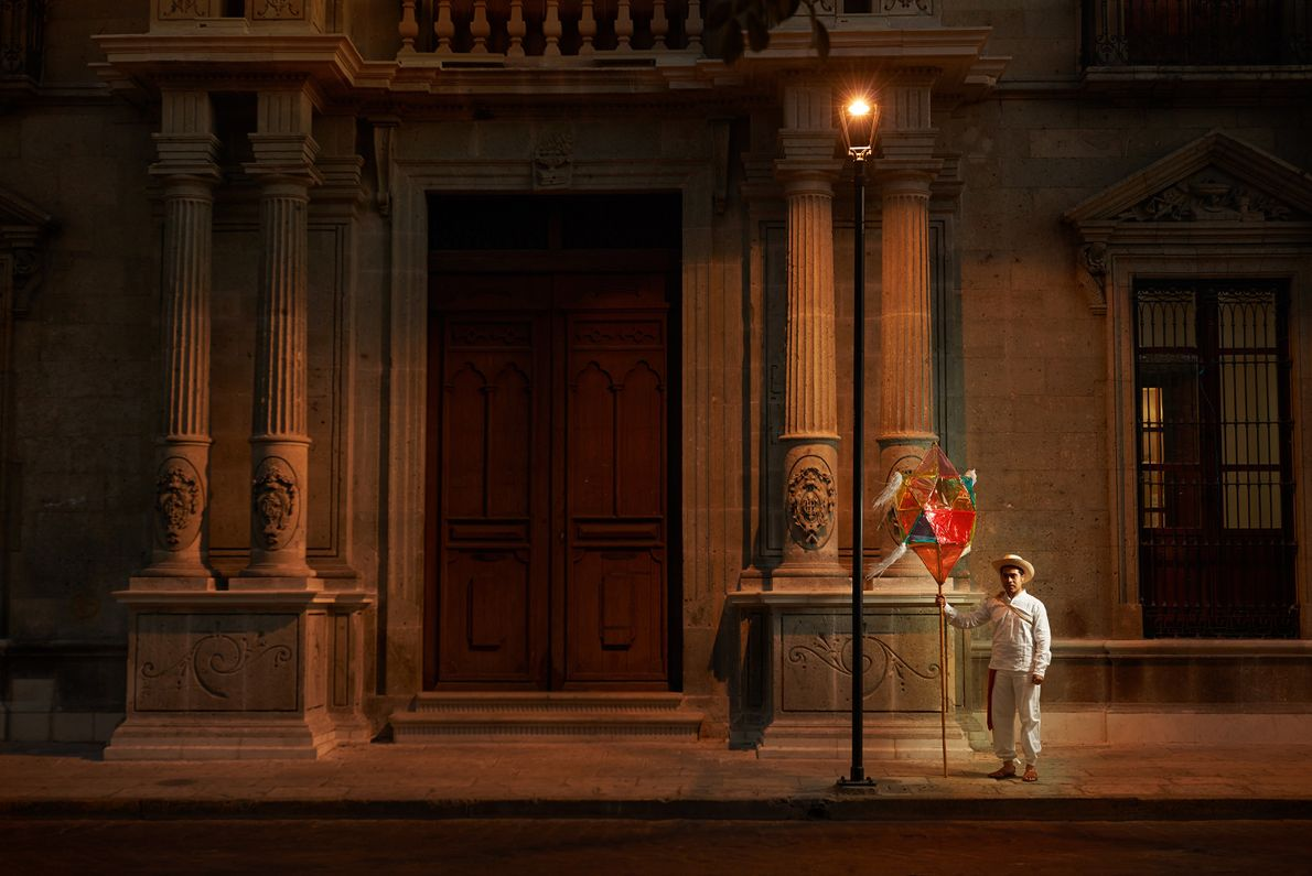 A lamplighter waits for a party to begin during the Guelaguetza festival, which takes place on ...