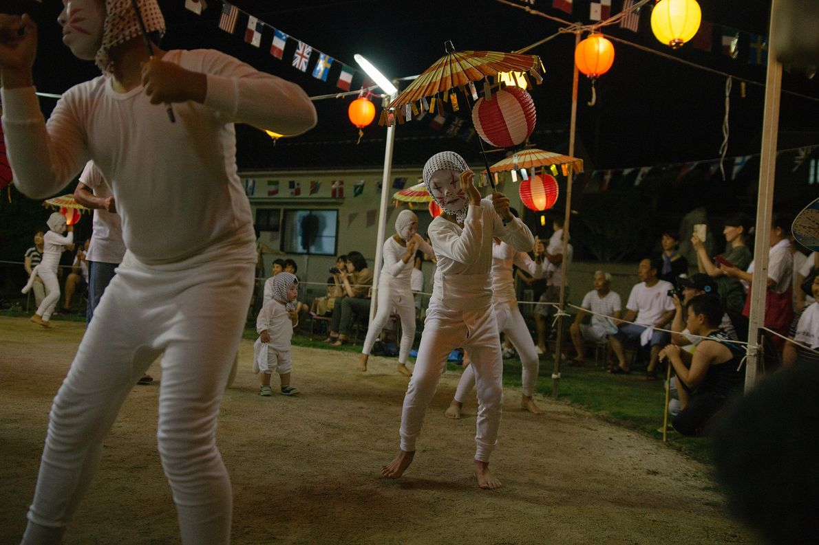 A group of kitsune perform the Bon Dance to the beat of a drum. People often ...