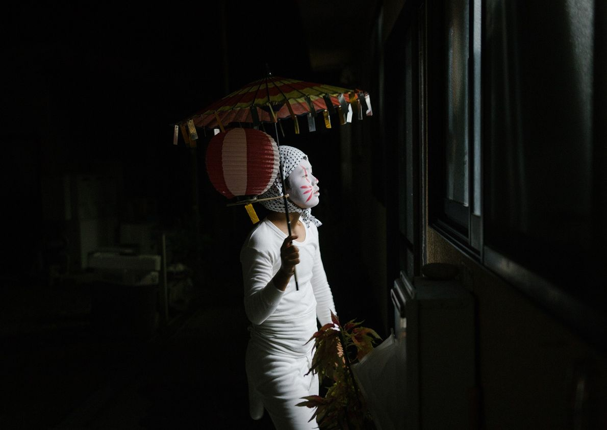 A child dressed as a kitsune, or fox, peers inside a neighbour's house during Obon festival. ...