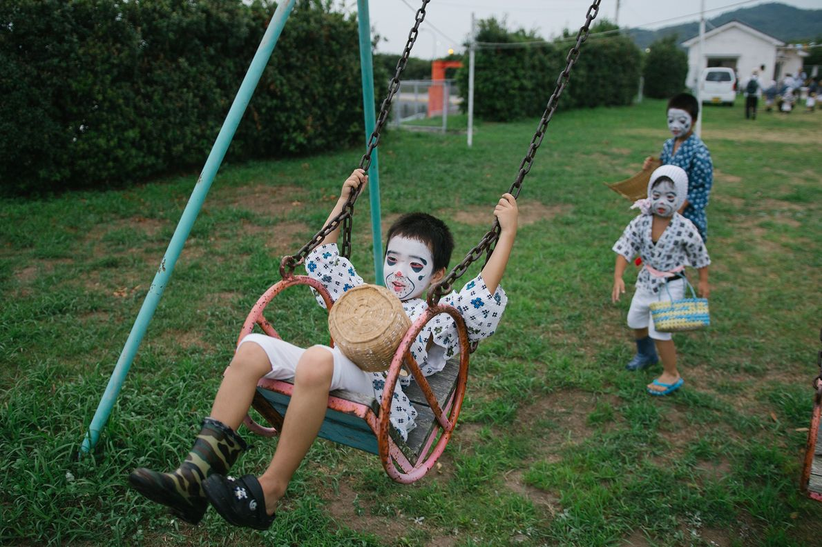 "Children dressed as ""drunk fishermen"" play outside during the Obon summer festival."