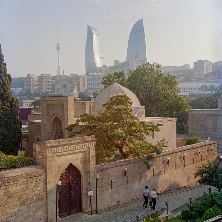 The sun shines over Baku's Presidential Palace and the Flame Towers, as seen from the medieval ...