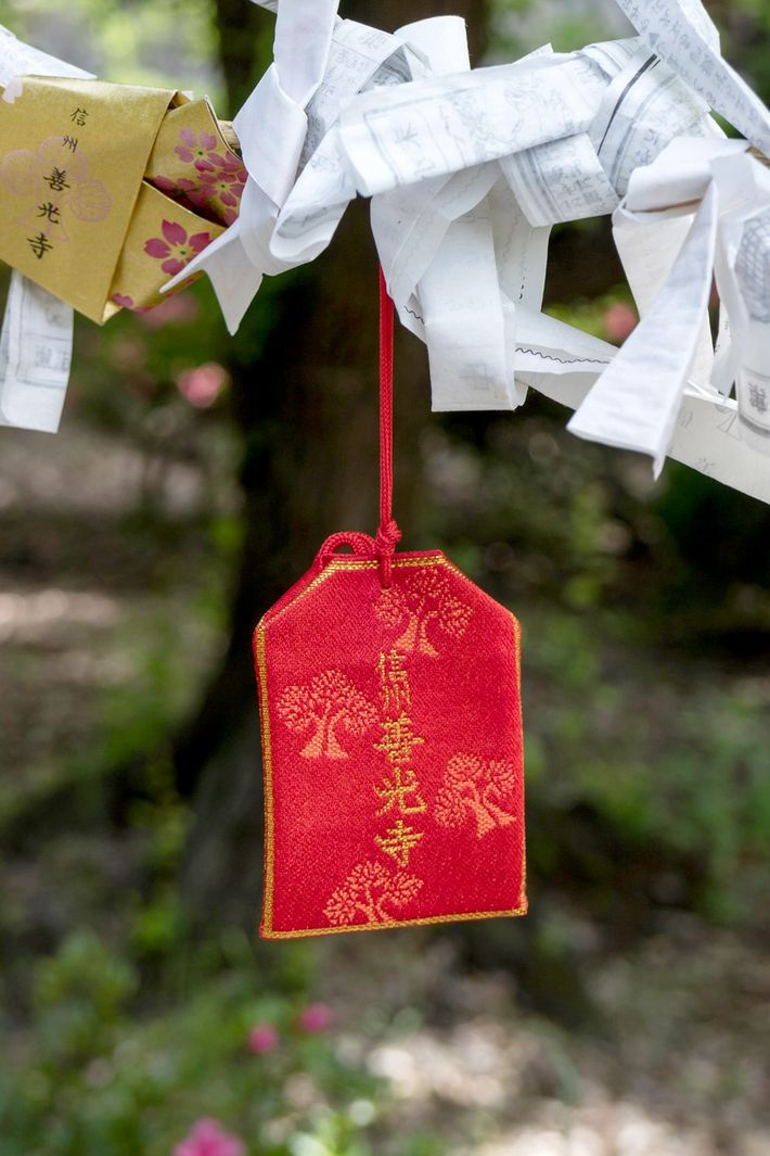 An omamori, a silk pouch which holds prayers, hangs near a temple in Nagono, Japan.