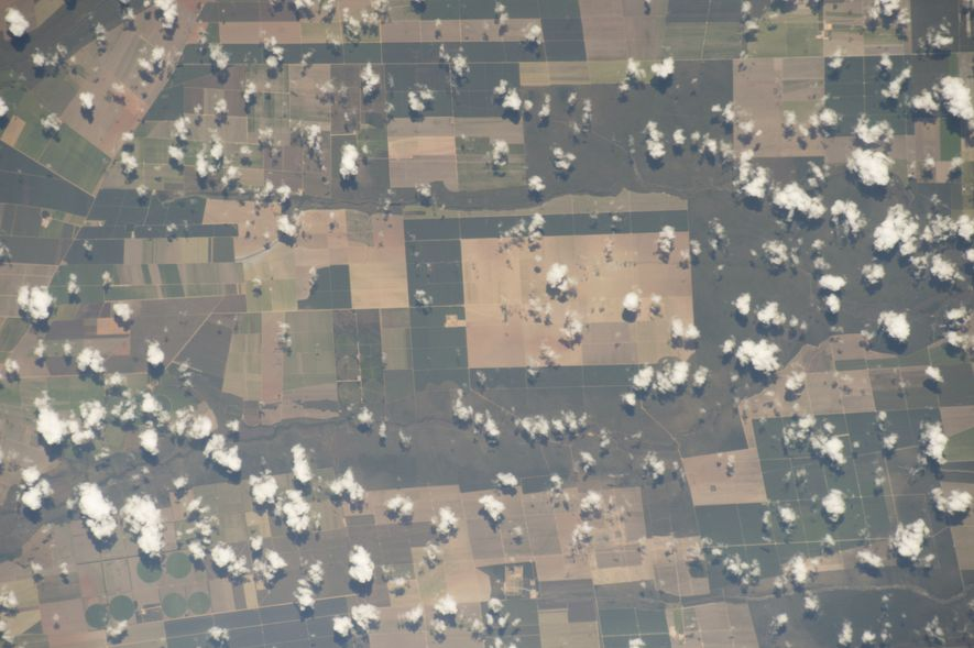 Cotton ball clouds dot farm fields in central Brazil.