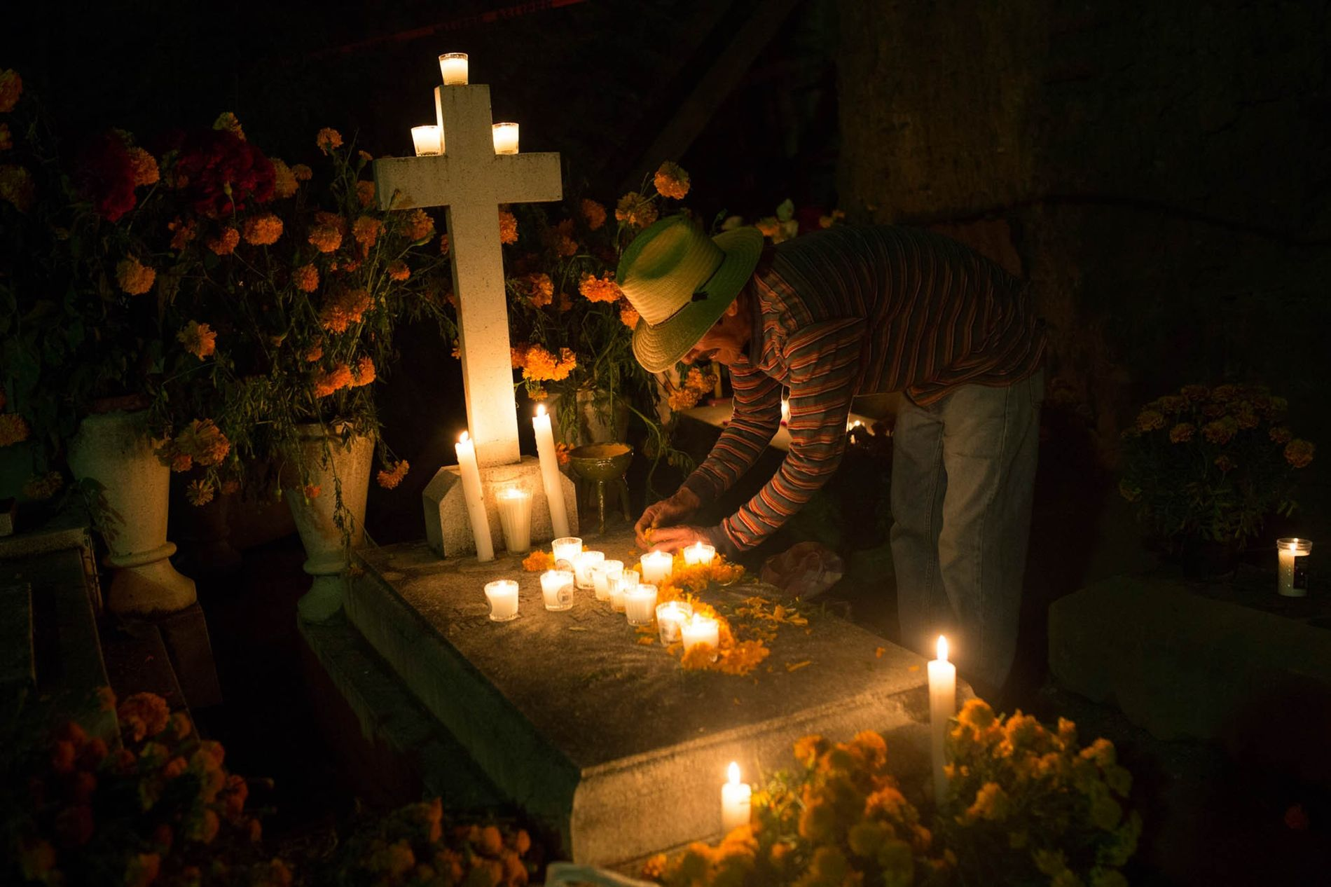 Catarano Cardova decorates his family grave with candles and flowers in Panteon Viejo Xoxocotlán.