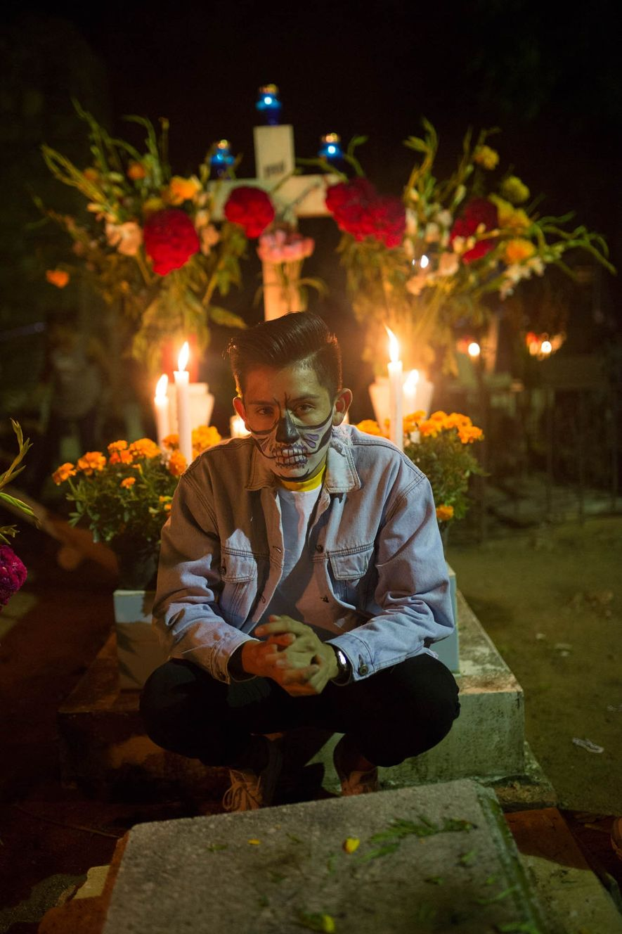 Rey Baltazer sits on a grave decorated with candles and flowers in Panteon Viejo Xoxocotlán on Day of the Dead, when people of all ages paint their faces to resemble calaveras, or skulls.