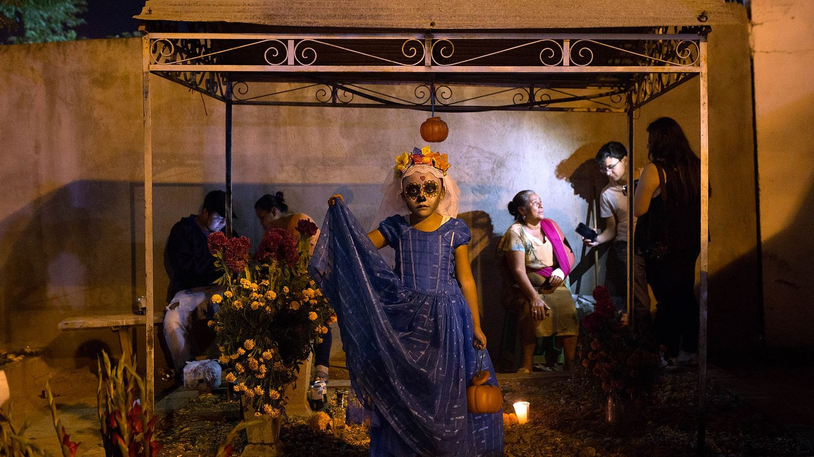 A young girl, Margarita Jimenez, dressed as a skeleton stands on a grave in Panteón Xoxocotlán. ...