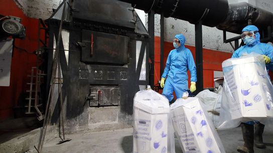 Workers in Kyiv, Ukraine, dispose of used medical masks and gloves by burning them in an ...