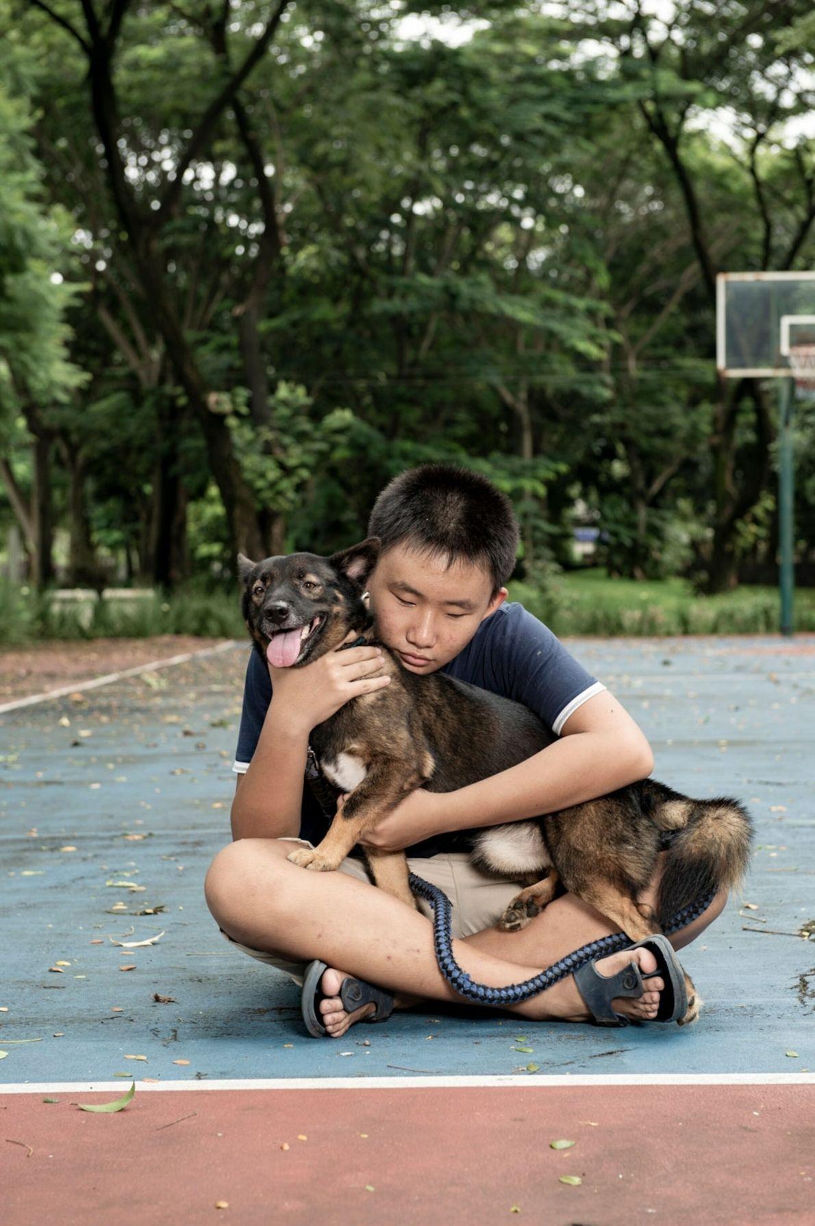 Hugo Gan, 15, a cousin of photographer Joshua Irwandi, plays with his four-year-old German shepherd mix, ...