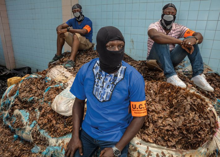 Masked to protect their identities, law enforcement officers with Côte d'Ivoire's organized crime unit sit atop ...