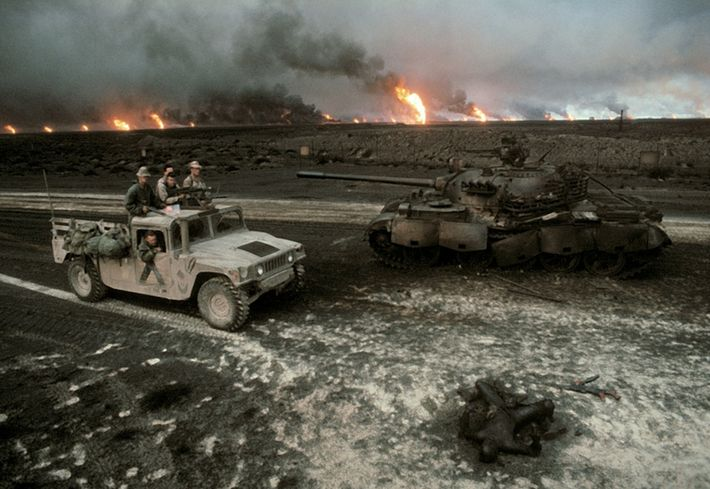 A U.S. patrol approaches a destroyed Iraqi tank and a charred corpse. Coalition forces liberated Kuwait ...