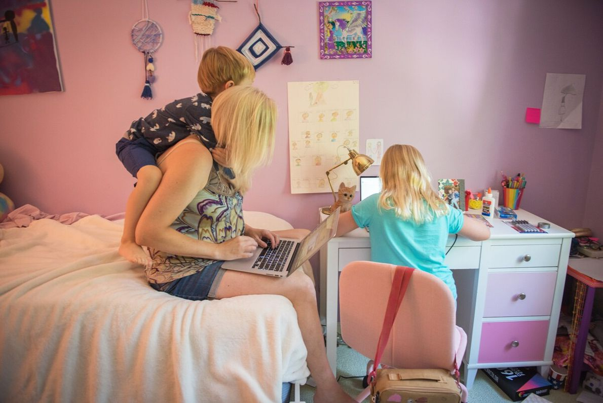 Draped by her toddler son, a mother works from home while her daughter attends her first ...