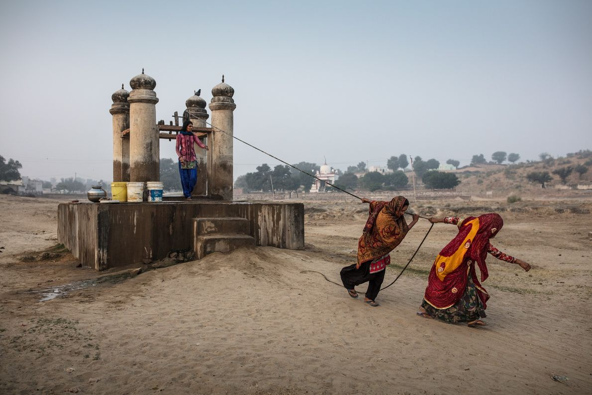 Women strain to haul precious water from a well in Dongra, in India's desert state of ...