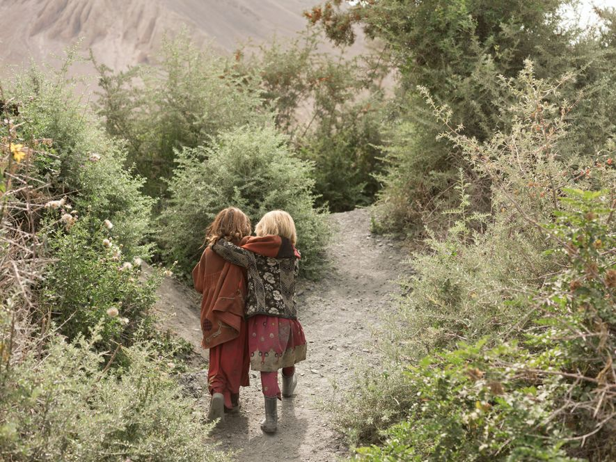 Anor Gul, six, at left, and Gul Shira, seven, head out to join other children gathering ...
