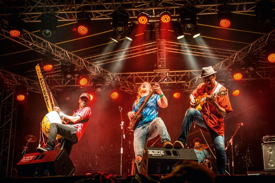 Guinean singer Djeli Moussa Condé (left) and his band performing at the Rainforest World Music Festival ...