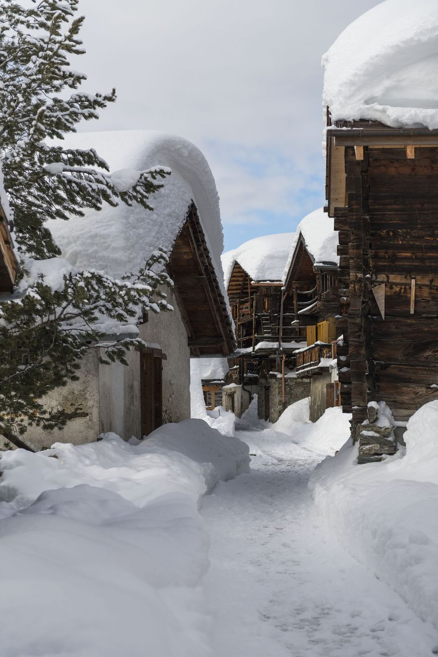 Snow-covered chalet roofs in quiet and remote Chandolin, one of the lesser-kwon villages in the Swiss Valais region.