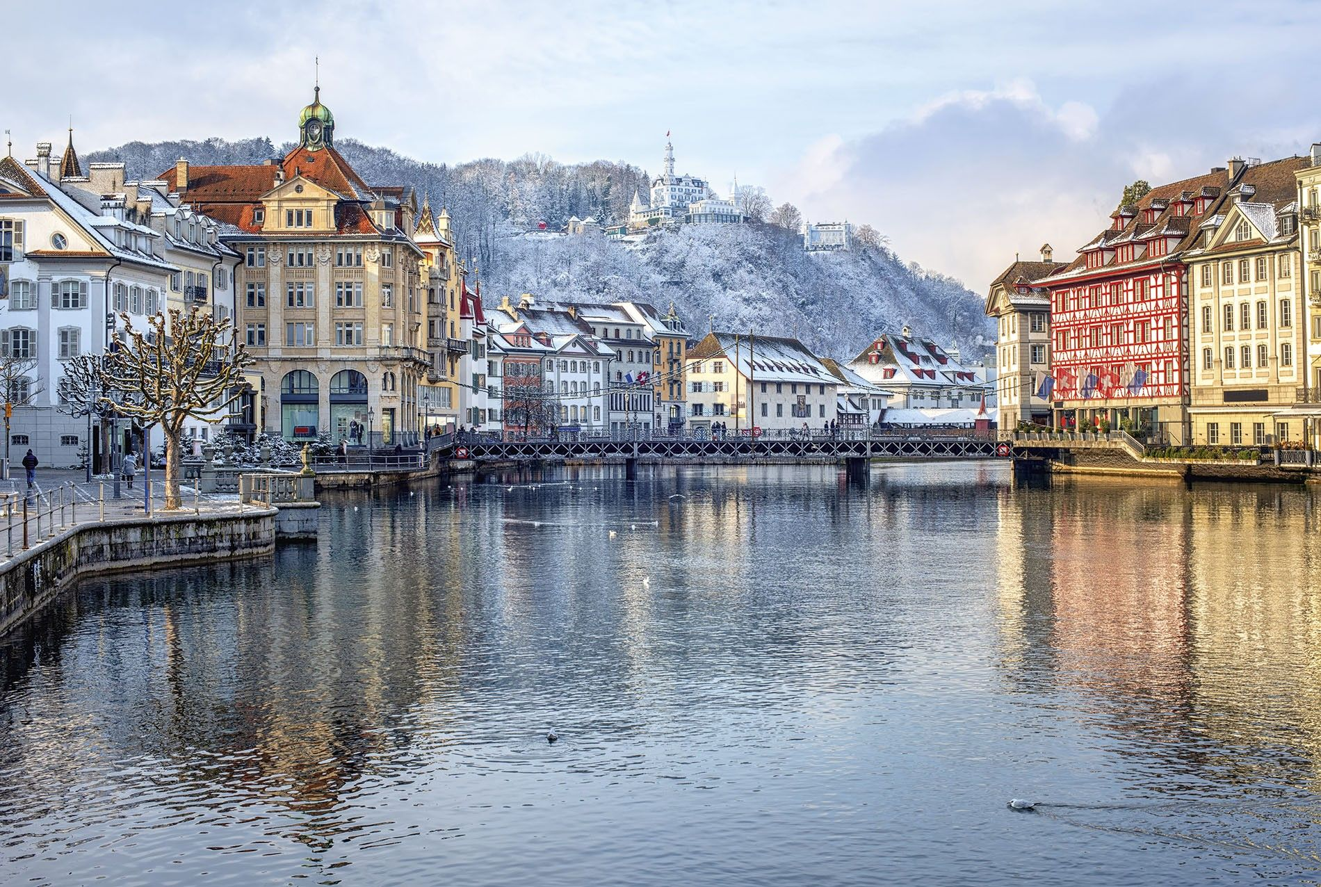 The Reuss river running through the picturesque old-town of Lucerne, in Switzerland, with its pastel-coloured houses and snowy mountains in the backdrop.