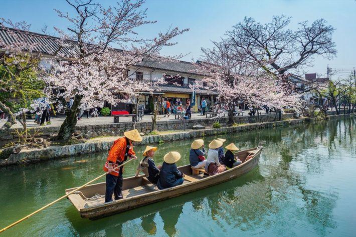 Visitors enjoying a canal boat journey in Kurashiki Bikan Historical Quarter in the city of Okayama.