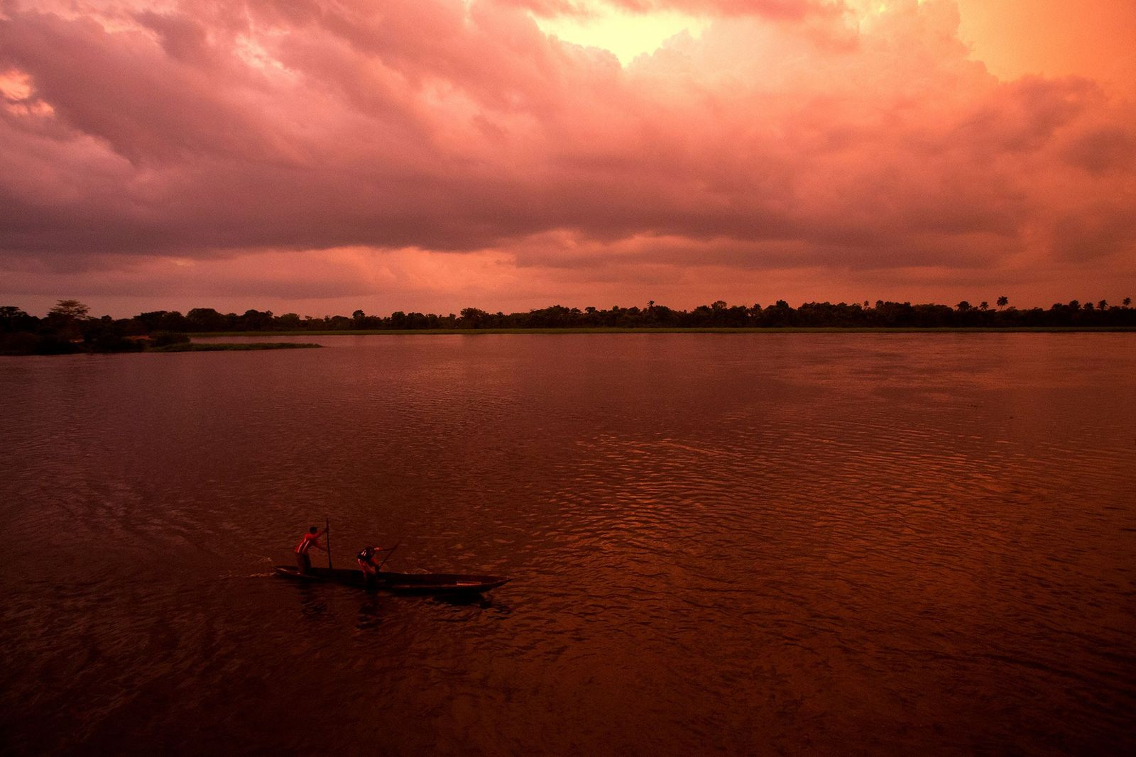 Two men paddle a canoe o​n the Congo River.