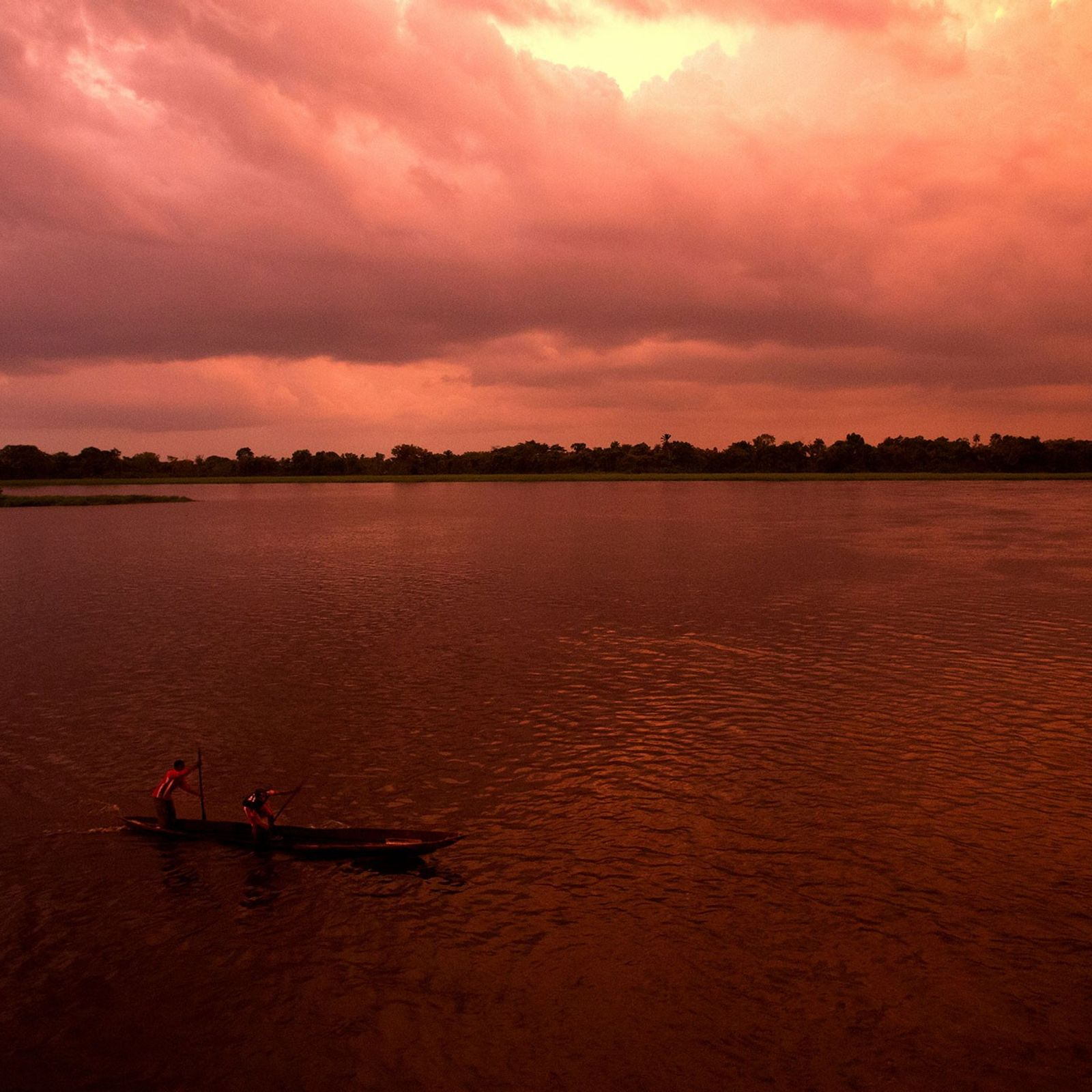 Two men paddle a canoe on the Congo River.