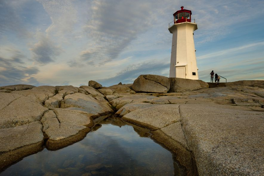 At sunset, the distinctive red light of the lighthouse at Peggy's Cove starts to glow.