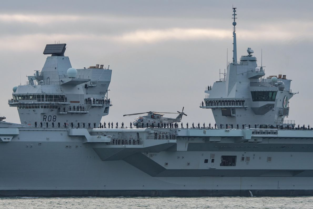 Ship personnel gather on deck in ceremonial formation as HMS Queen Elizabeth leaves Portsmouth for the ...
