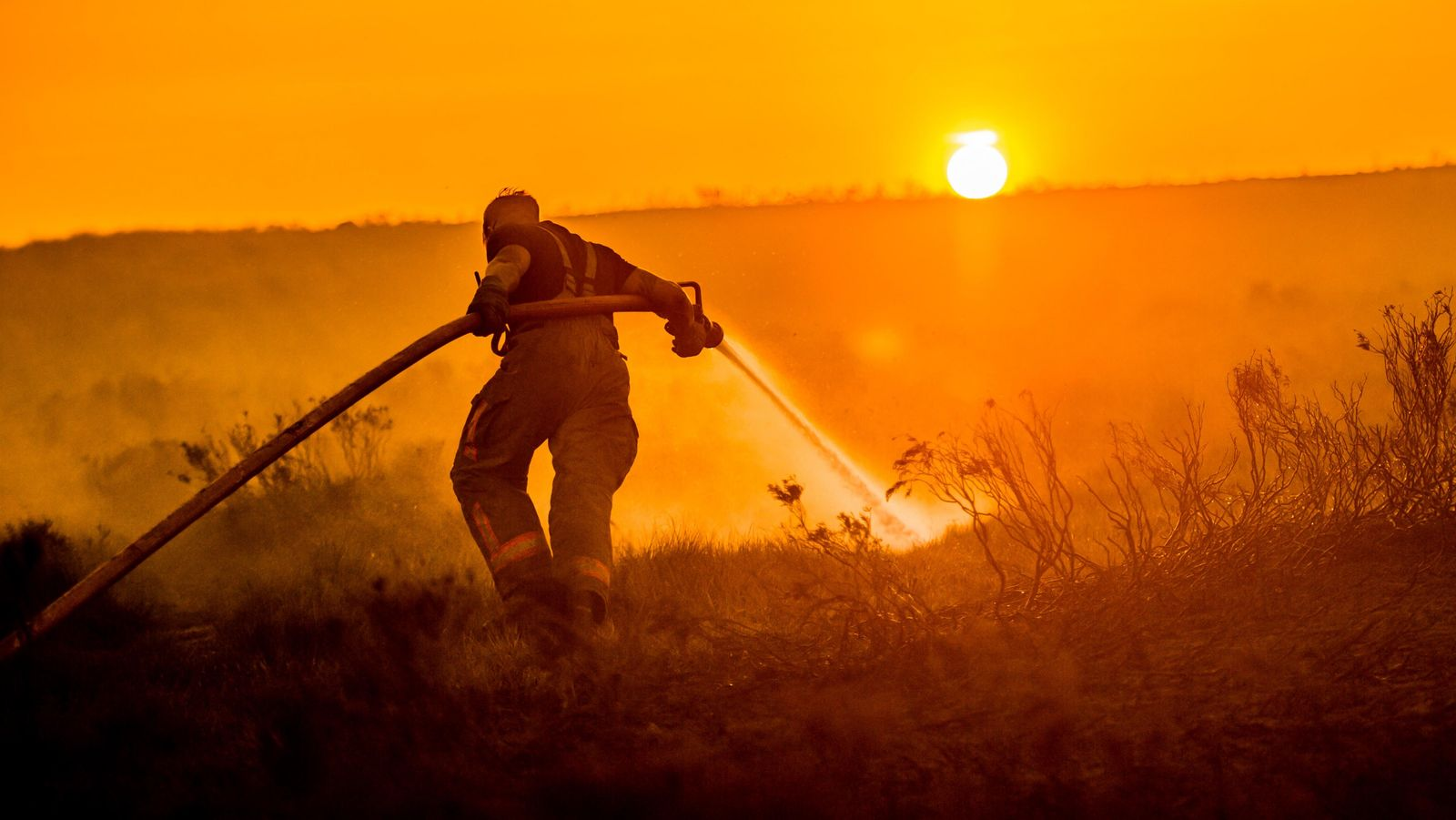 Saddleworth Moor, 2018. Fire fighters damp down the burning moorland above Carrbrook, during a three-week wildfire on ...