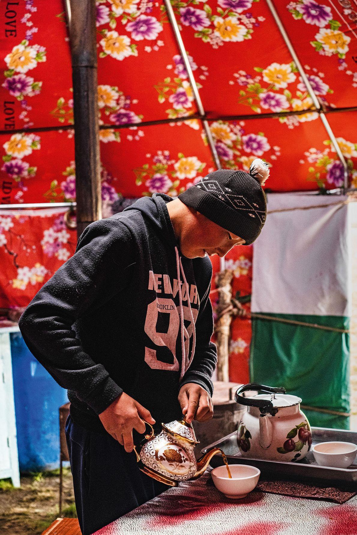 Umutkor's older son, Nurbek, pours tea. In Kyrgyz households, tea is nearly as popular a drink ...
